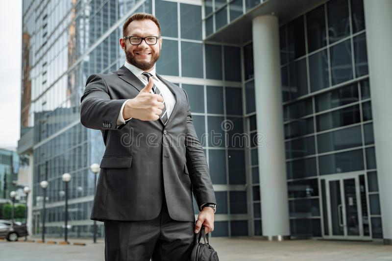 Portrait of a happy business man showing his thumb up on the background of the business center royalty free stock photography