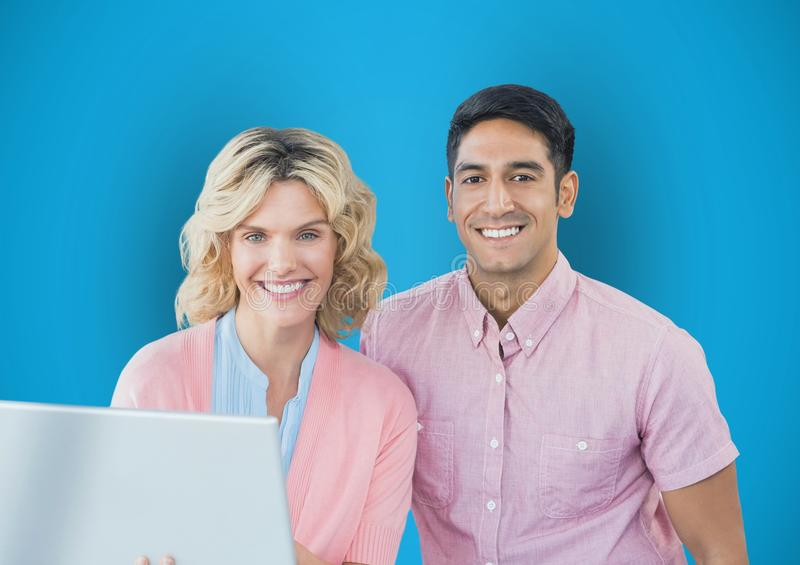Portrait of happy business people with laptop against blue background royalty free stock photography