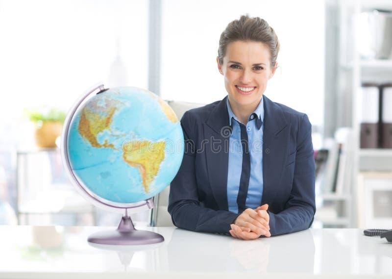Portrait of happy business woman near earth globe stock photos