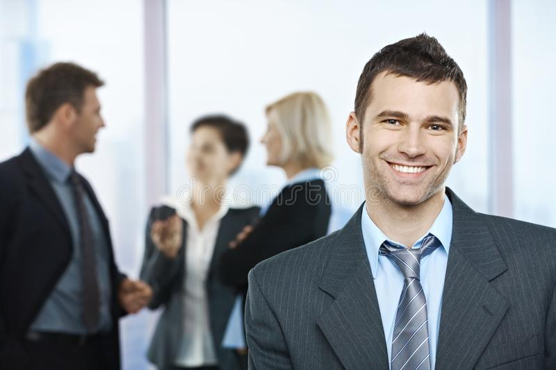 Portrait of happy businessman. With coworkers talking in the background stock photography