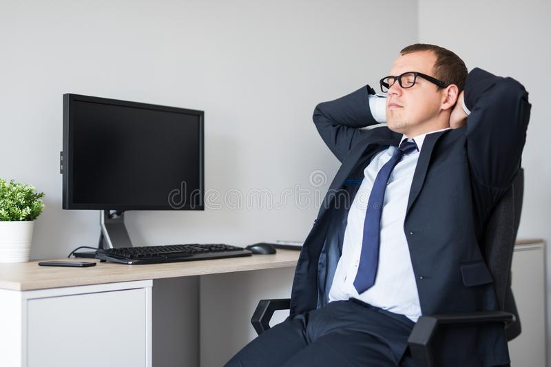Happy businessman relaxing in modern office and blank pc screen with copy space royalty free stock photography