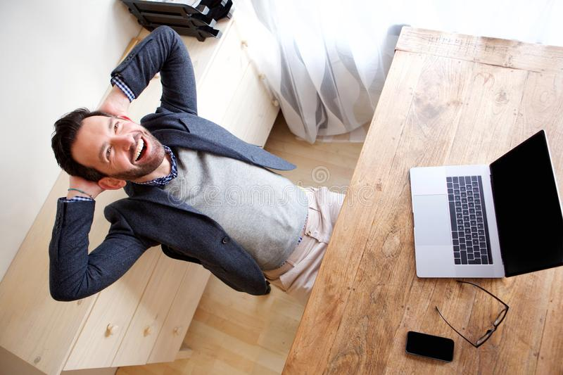 Happy businessman relaxing in office with laptop. Portrait of happy businessman relaxing in office with laptop stock photo
