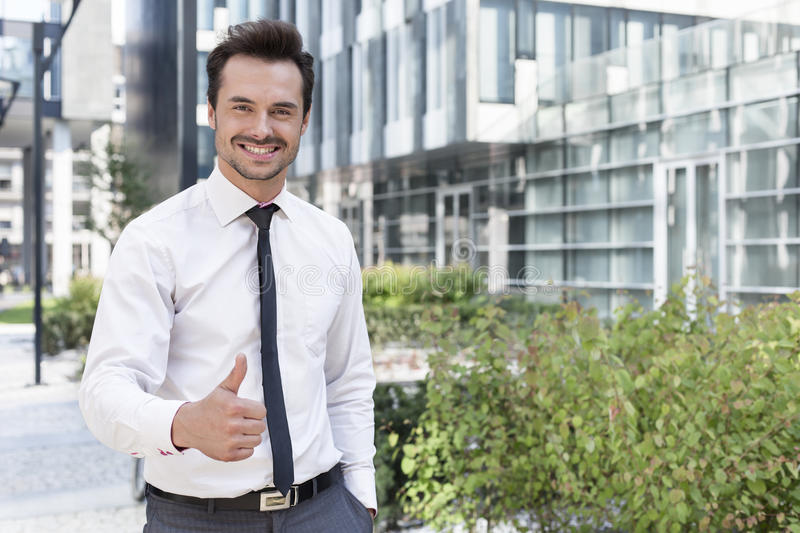 Portrait of happy businessman showing thumbs up outside office building royalty free stock photography