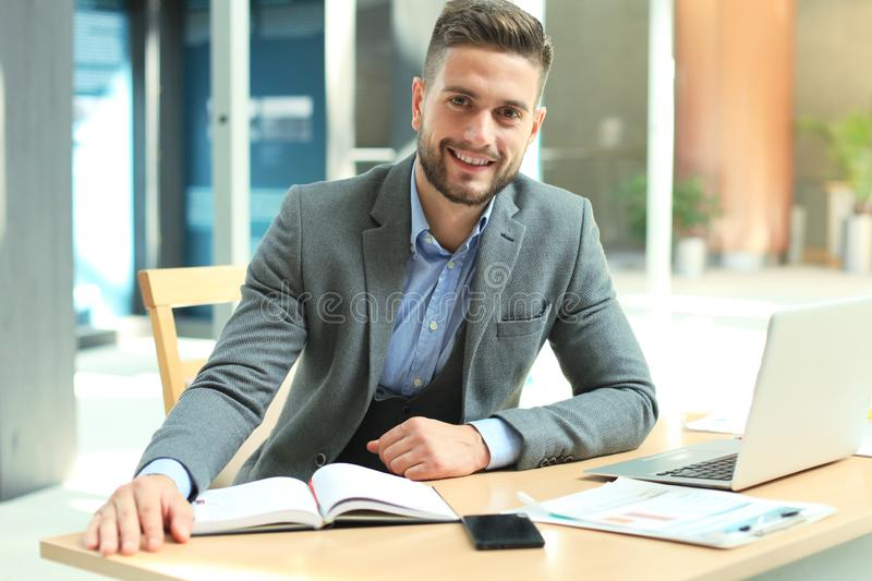 Portrait of happy businessman sitting at office desk, looking at camera, smiling. stock image