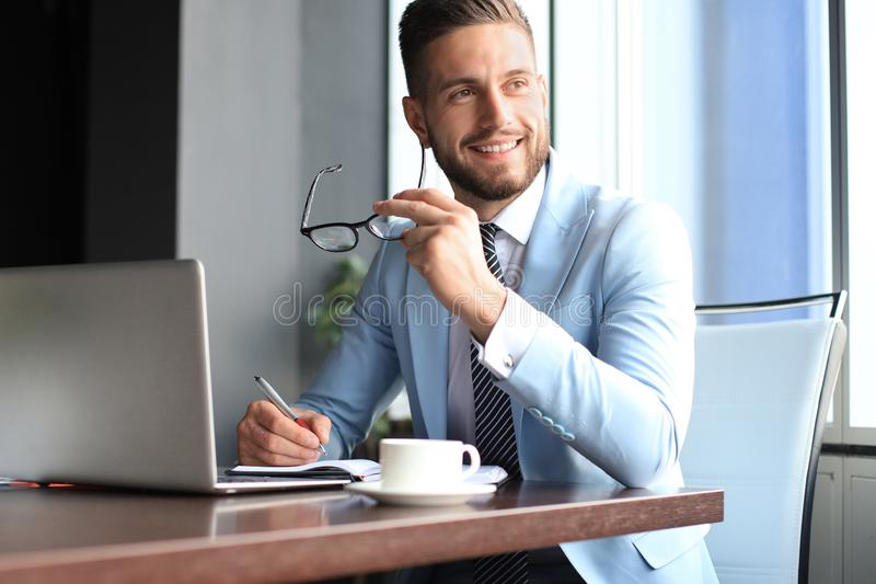 Portrait of happy businessman sitting at office desk, looking at camera, smiling royalty free stock image