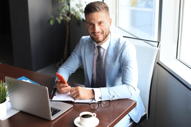 Portrait of happy businessman sitting at office desk, smiling stock photo