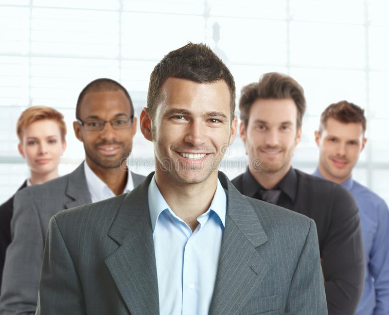 Portrait of happy businessman and team stock image