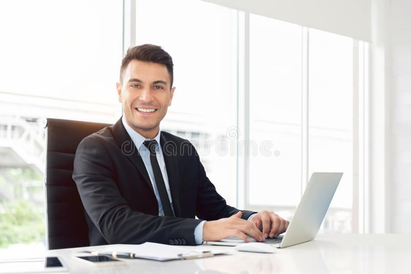 Portrait of a Happy businessman working on laptop stock image