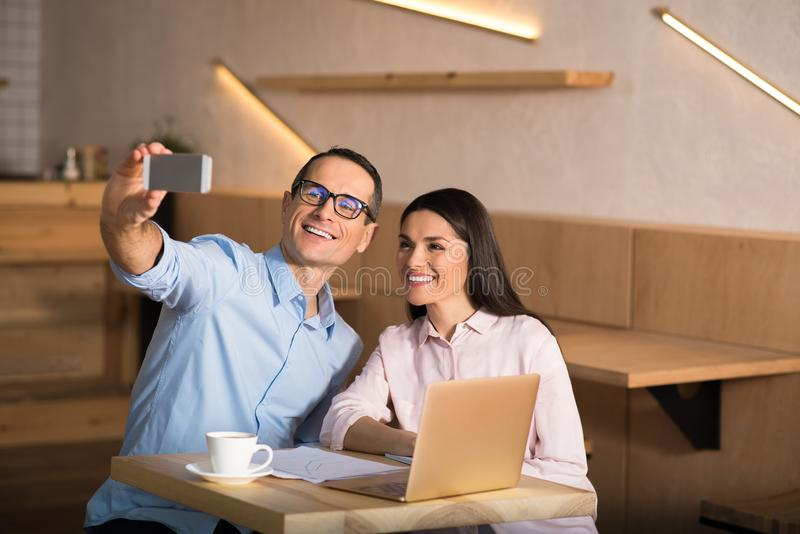 Businesspeople taking selfie on smartphone. Portrait of happy businesspeople taking selfie on smartphone in cafe stock photos