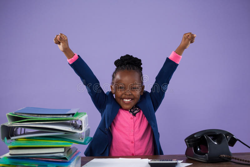 Portrait of happy businesswoman with arms raised at desk stock image