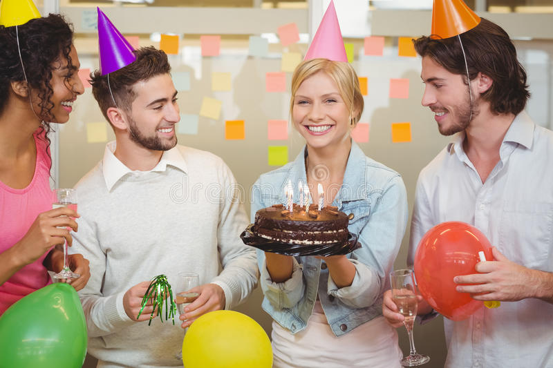 Portrait of happy businesswoman holding birthday cake. While colleagues looking at her in creative office stock image
