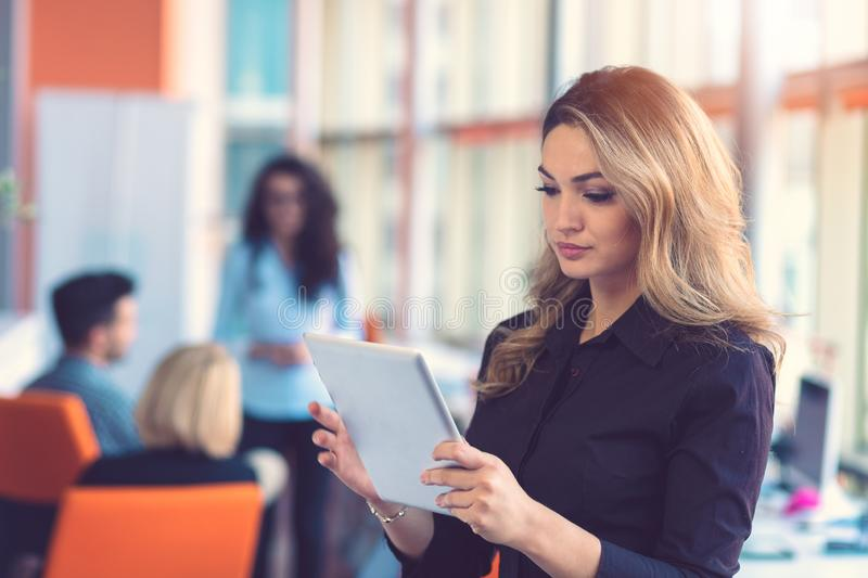 Portrait of happy businesswoman holding digital tablet in office standing in front of colleagues discussing at stock photos