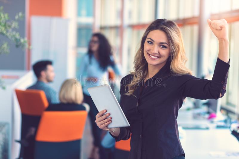 Portrait of happy businesswoman holding digital tablet in office standing in front of colleagues discussing at stock image