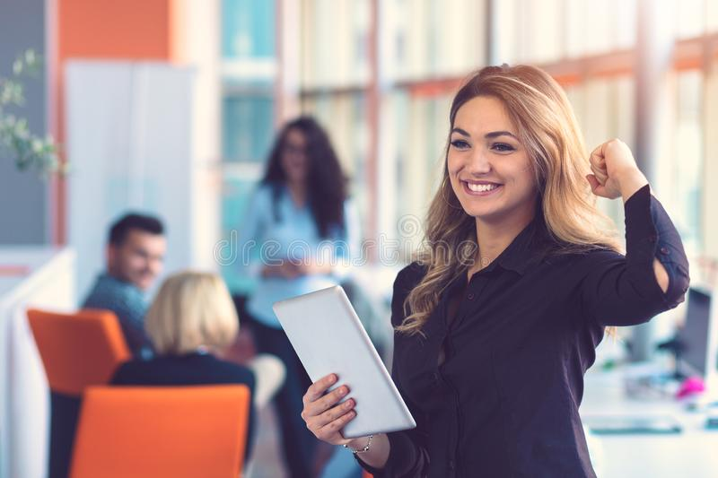 Portrait of happy businesswoman holding digital tablet in office standing in front of colleagues discussing at royalty free stock image