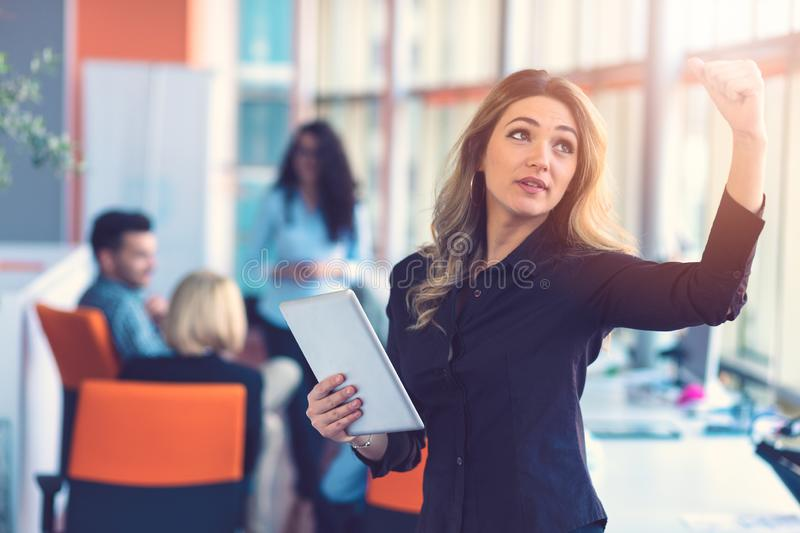 Portrait of happy businesswoman holding digital tablet in office standing in front of colleagues discussing at royalty free stock photos