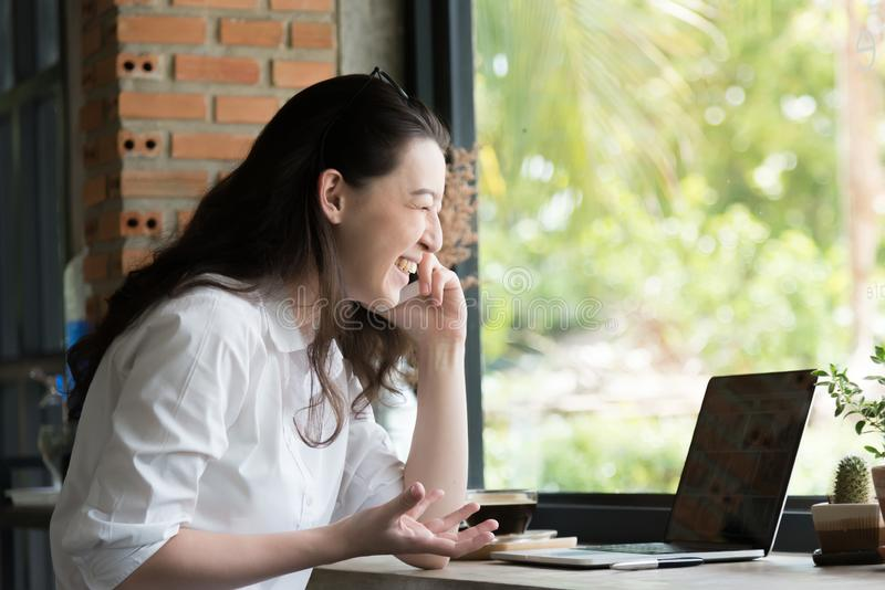 Portrait of a happy businesswoman sitting and use internet smartphone with laptop computer at her workplace office royalty free stock photography