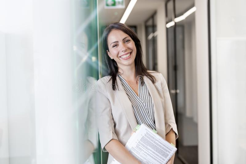 Portrait of happy businesswoman standing with documents by wall at office stock photography