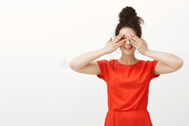 Portrait of happy carefree Caucasian girl with curly hair in stylish red dress, covering eyes with palms and smiling stock photography