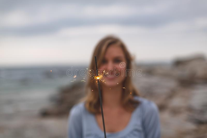 Caucasian woman standing with sparkle at beach stock photography
