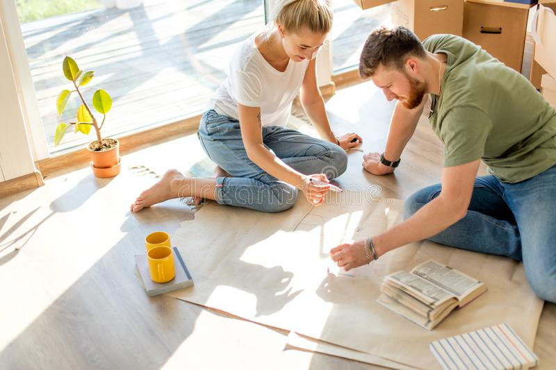 Couple looking blueprints of they new house. Planning interior design royalty free stock photography