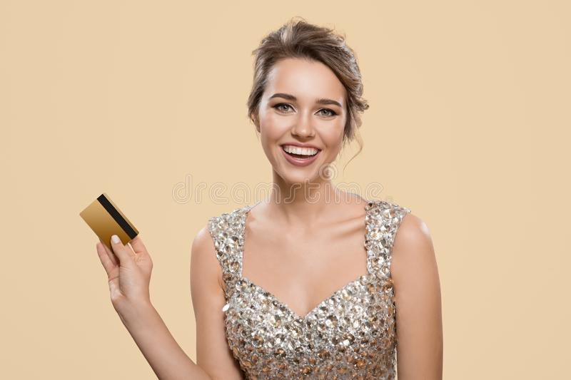 Portrait of happy charming woman holding gold plastic bank card. stock photo