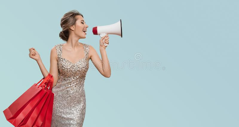 Portrait of happy charming woman holding red shopping bags. Shout into megaphone on copyspace. Blue background stock photography