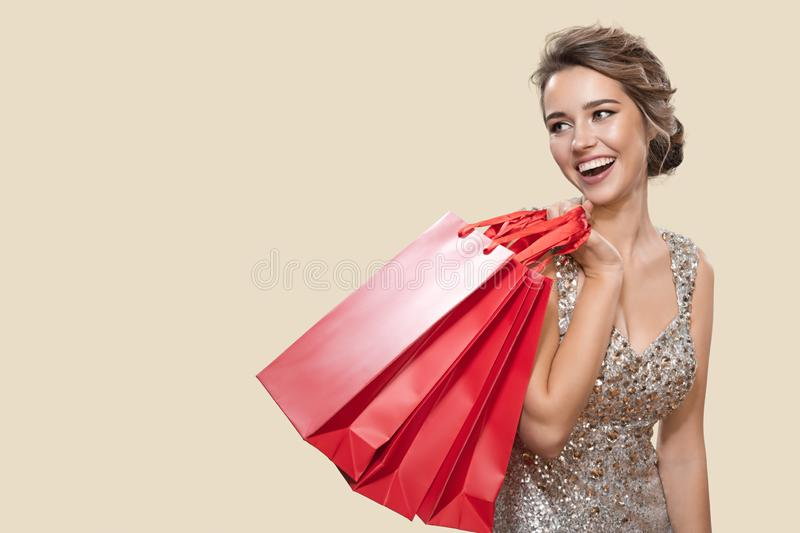 Portrait of happy charming woman holding red shopping bags. Yellow background royalty free stock image