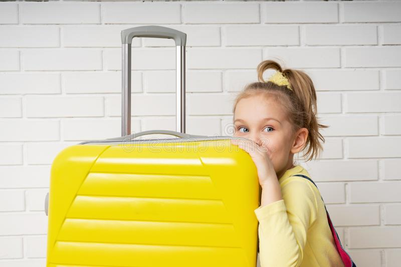 Happy cheerful child tourist girl with a yellow suitcase for traveling, relaxing, peeking inside a bag and wondering content. Portrait of a happy cheerful child royalty free stock photography
