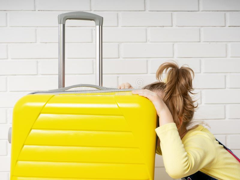 Happy cheerful child tourist girl with a yellow suitcase for traveling, relaxing, peeking inside a bag and wondering content. Portrait of a happy cheerful child stock image