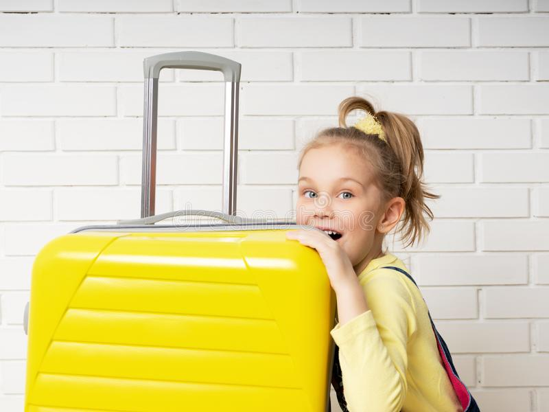 Happy cheerful child tourist girl with a yellow suitcase for traveling, relaxing, peeking inside a bag and wondering content. Portrait of a happy cheerful child royalty free stock image