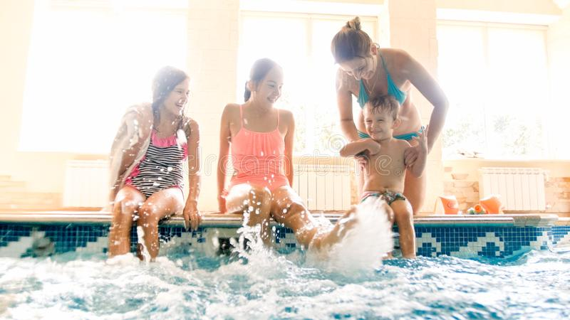Portrait of happy cheerful family sitting on the poolside and splashing water with feet. Family playing and having fun stock photography