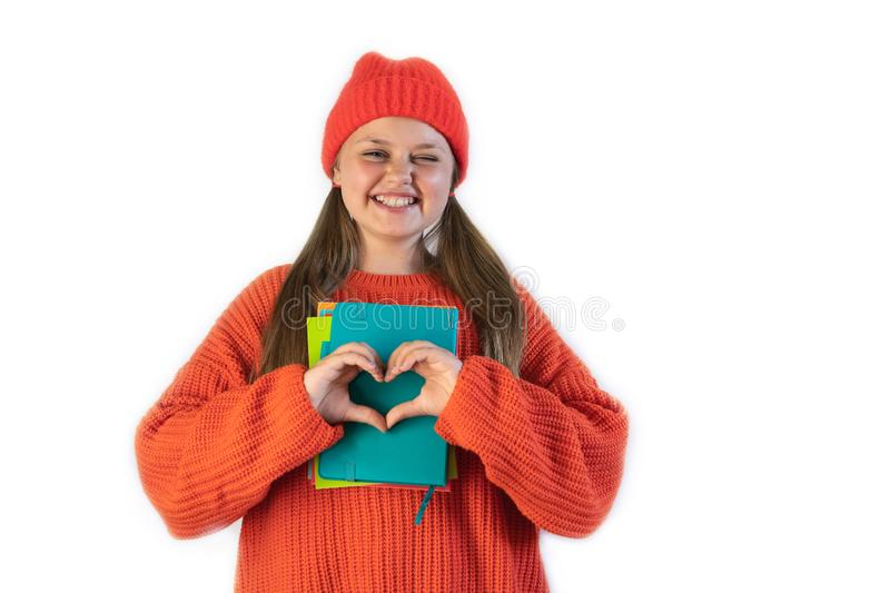 Portrait of a happy cheerful girl in winter red hat showing heart with two hands royalty free stock image