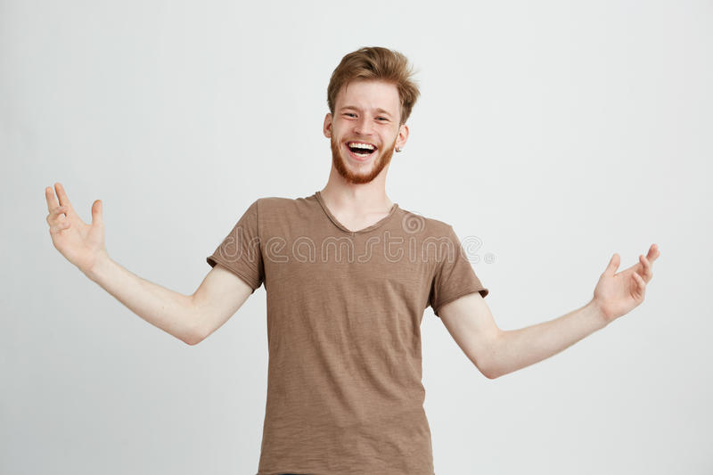 Portrait of happy cheerful positive young man laughing rejoicing gesturing looking at camera over white background. royalty free stock images