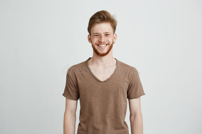 Portrait of happy cheerful young man with beard smiling looking at camera over white background. Copy space royalty free stock photography