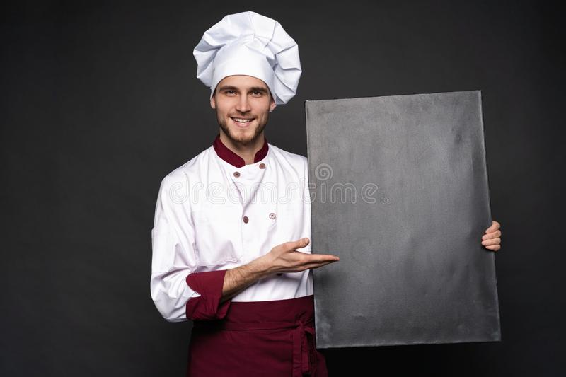 Portrait of a happy chef cook showing copyspace on the palms isolated on black background. Portrait of a happy chef cook showing copyspace on the palms isolated stock photos