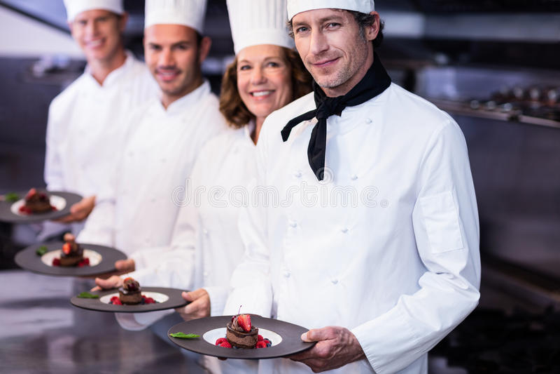 Portrait of happy chefs presenting their dessert plates stock photo