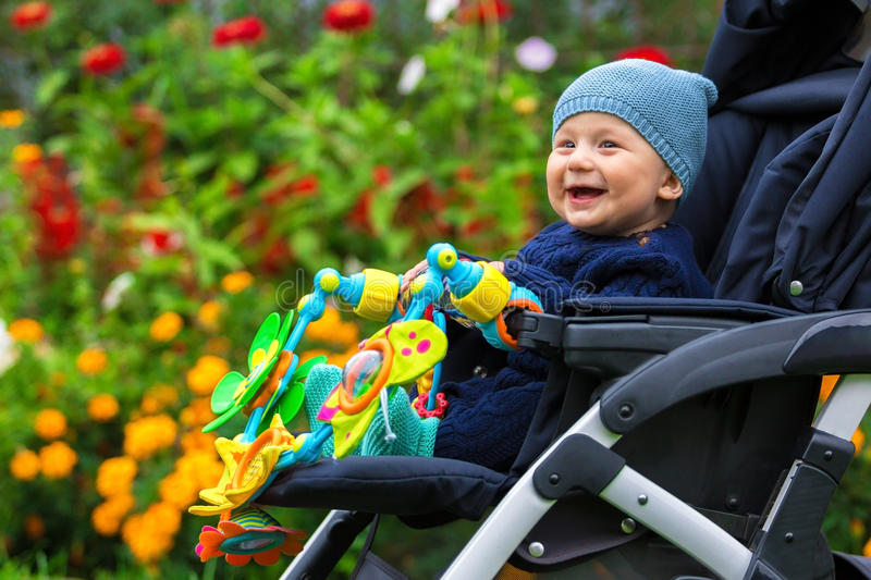 Portrait of a happy child in a baby carriage outdoors stock images