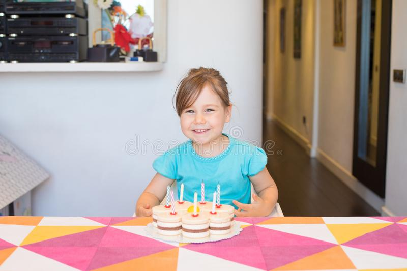 Portrait of happy child with birthday cake. Portrait of happy three years old blonde child smiling looking with birthday cake with candles on colorful tablecloth royalty free stock photography