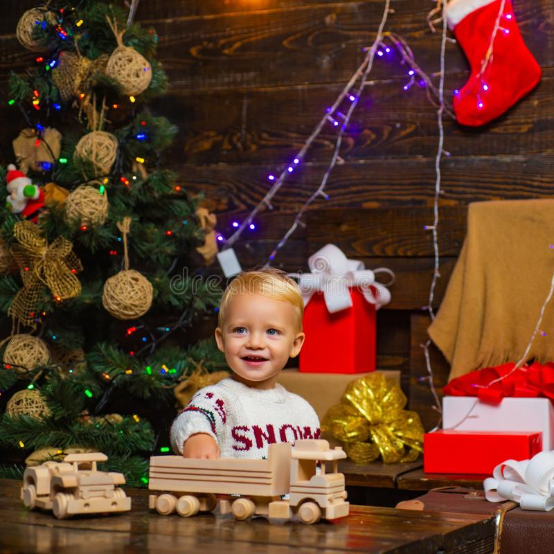 Portrait of happy child looking at decorative toy ball by Christmas tree. Kid enjoy the holiday. Happy little child stock image
