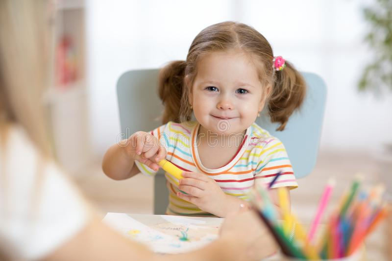 Portrait of happy child painting with pencils stock photo