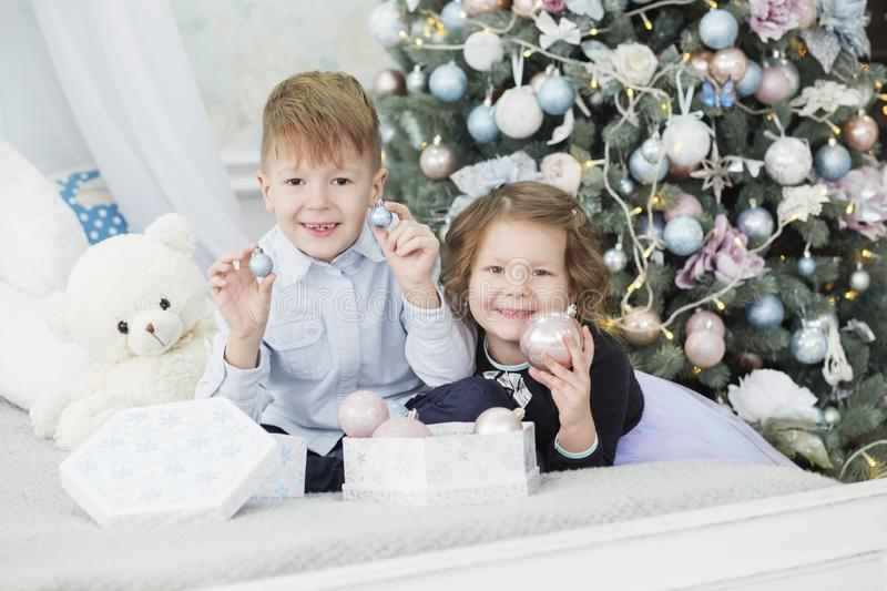 Portrait of a happy children - boy and girl. Little kids in Christmas decorations. Brother and sister royalty free stock images