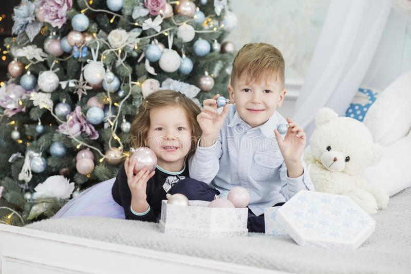 Portrait of a happy children - boy and girl. Little kids in Christmas decorations. Brother and sister. Decorate christmas tree royalty free stock image