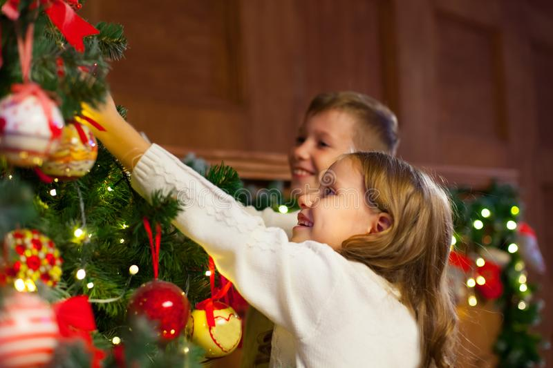 Portrait of happy children decorating Christmas tree.Family, chr. Istmas, winter,happiness and people concept stock photo