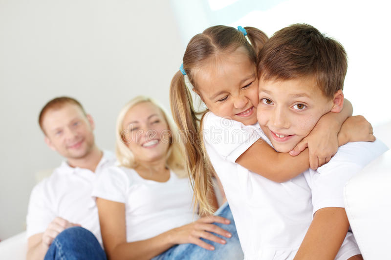 Tight embrace. Portrait of happy children in embrace with their parents behind royalty free stock images