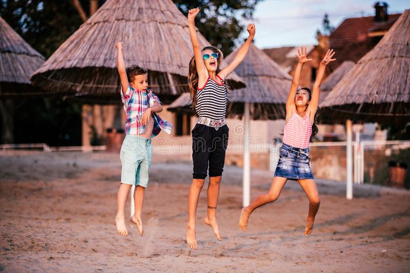 Happy children jumping on the sandy beach stock image