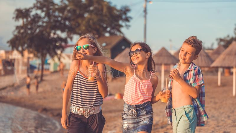 Portrait of happy children while having fun walking on the beach stock photos