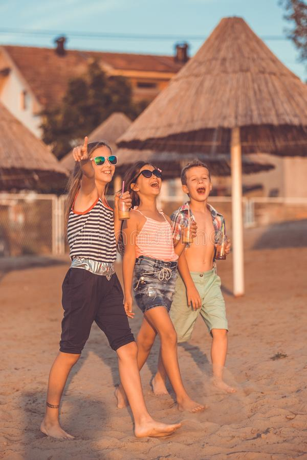 Happy children while having fun on the beach royalty free stock photo