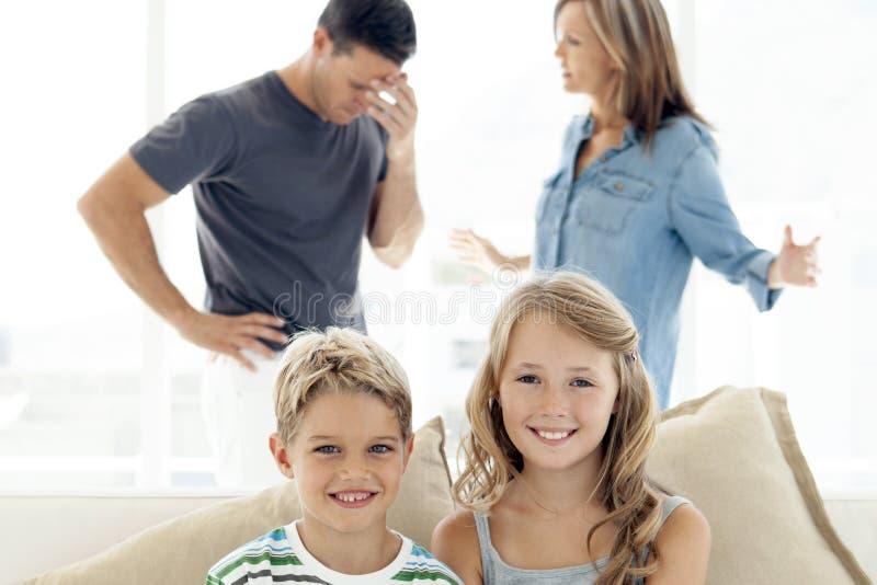 Portrait of happy children - parents arguing in background stock photo