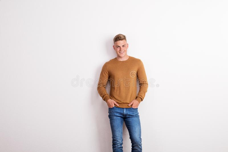 Portrait of a happy young man standing in a studio, hands in pockets. royalty free stock images