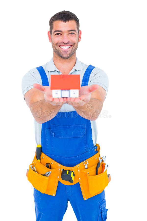 Portrait of happy construction worker holding house model stock images